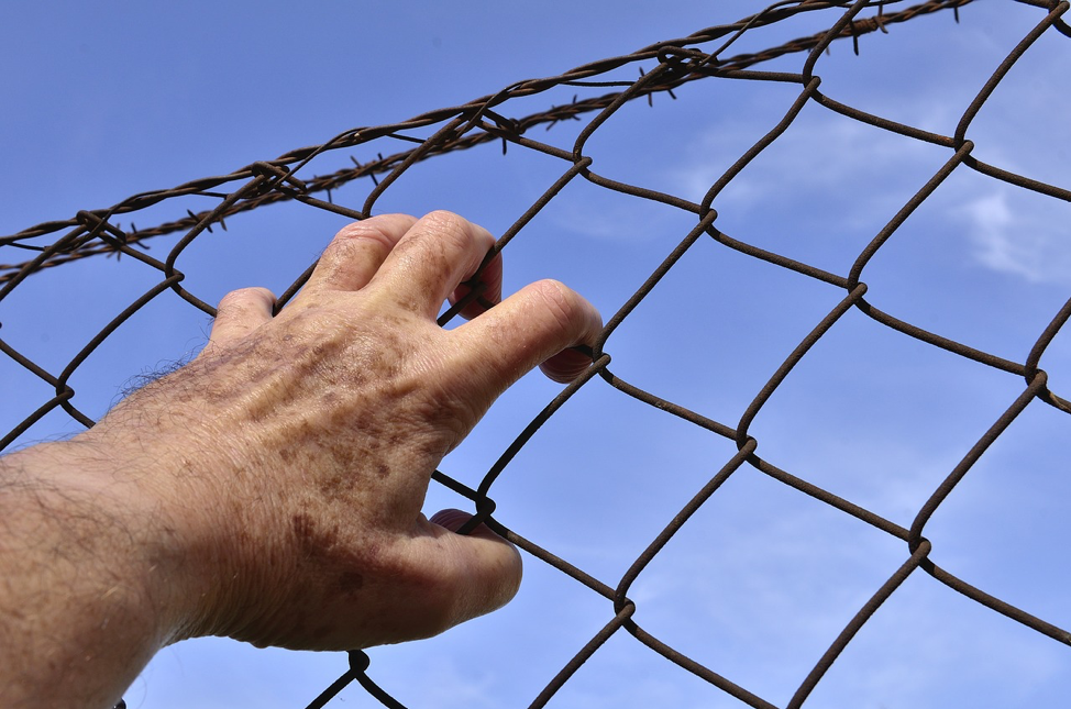 man grabbing fence. Supreme Court Finds Prisoner Risk Assessment Tests Biased
