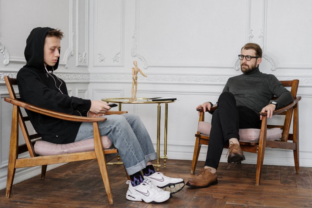 boy and man sitting in chairs