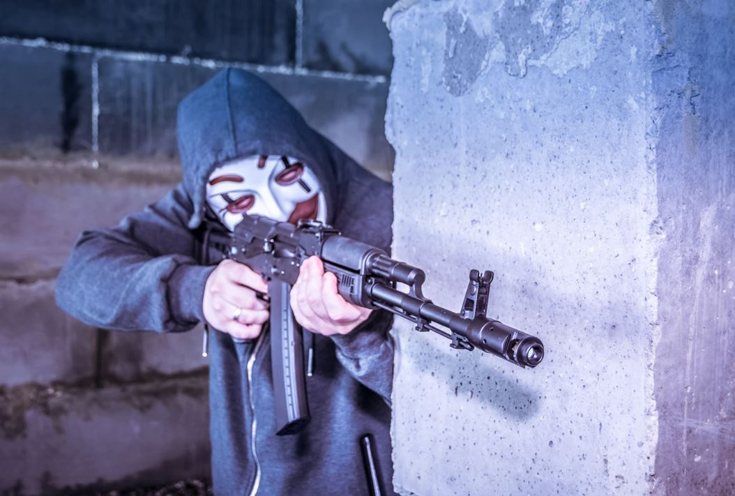 person with rifle wearing mask