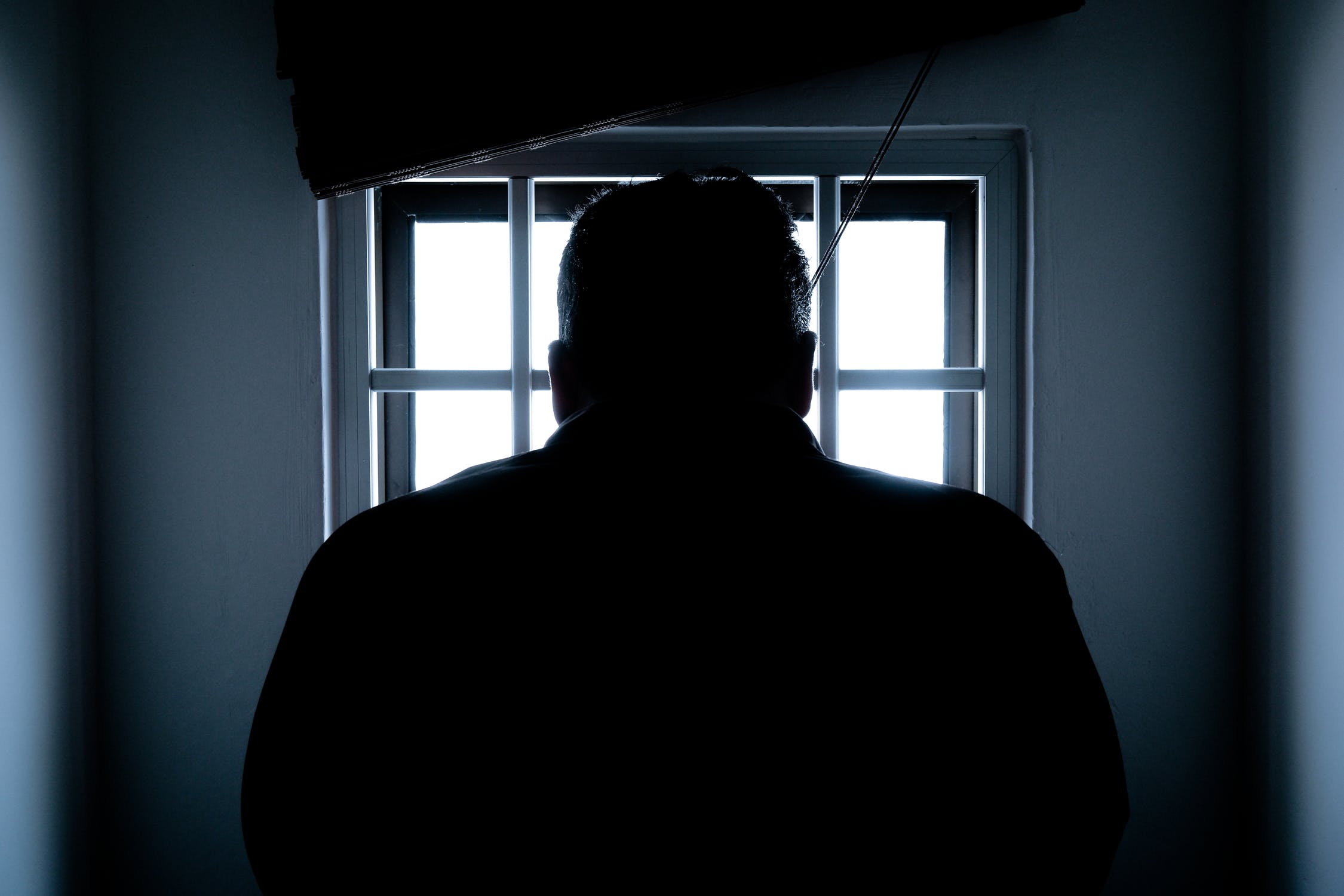 rear-view-of-a-silhouette-man-in-jail