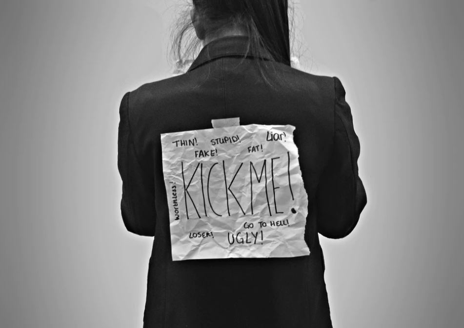 woman with Kick-Me sign in black and white